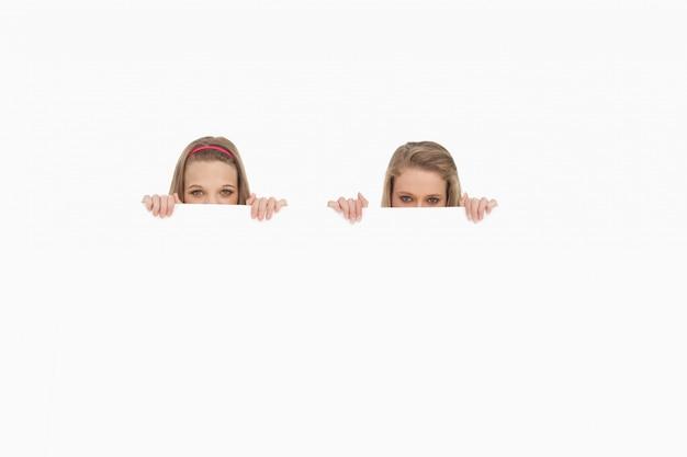 Close-up van jonge vrouwen die achter een leeg teken verbergen Premium Foto