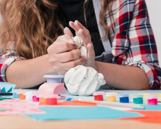 Close-up van jonge vrouwenhand die witte klei kneden Gratis Foto