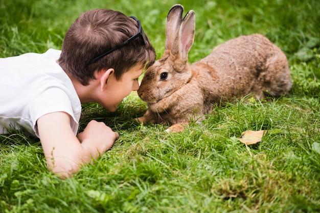 Close-up van jongen die op groen gras ligt dat in het oog van het konijn kijkt Gratis Foto
