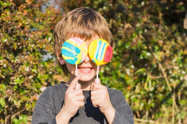 Close-up van jongen die twee lollys voor zijn ogen houdt Gratis Foto