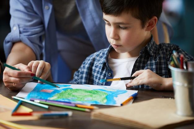 Close-up van jongen tekenen afbeeldingen met moeder Premium Foto