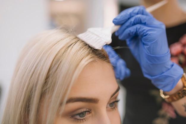 Close-up van kapper die kleurstof met borstel toepast Gratis Foto