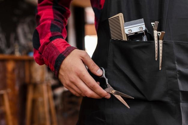 Close-up van kappershulpmiddelen in zwarte schort Gratis Foto