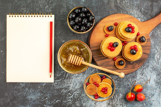 Close-up van karnemelk pannenkoeken met fruit, honing, fruit en notebook Gratis Foto