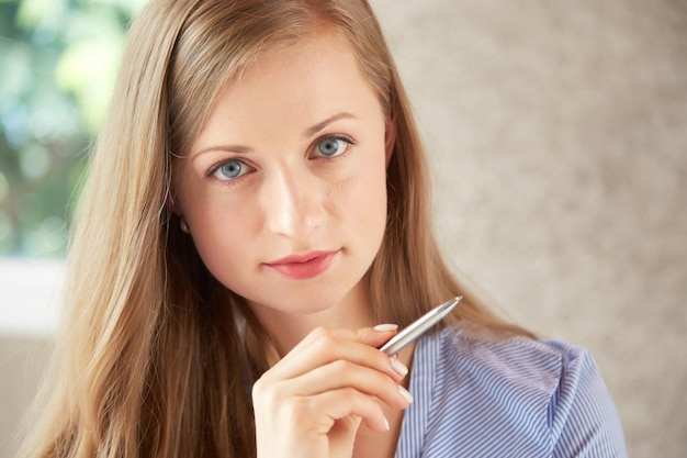 Close-up van kaukasische vrouw die de pen van de cameraholding bekijken Gratis Foto