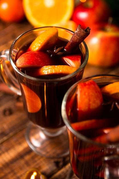 Close-up van kerstmis glühwein met fruit, kaarsen en kruiden achtergrond Premium Foto