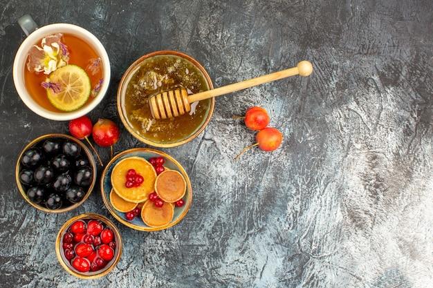 Close-up van klassieke pannenkoeken geserveerd met honing en een kopje thee Gratis Foto