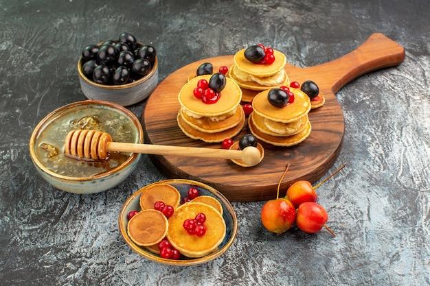 Close-up van klassieke pannenkoeken op snijplank honing en fruit Gratis Foto