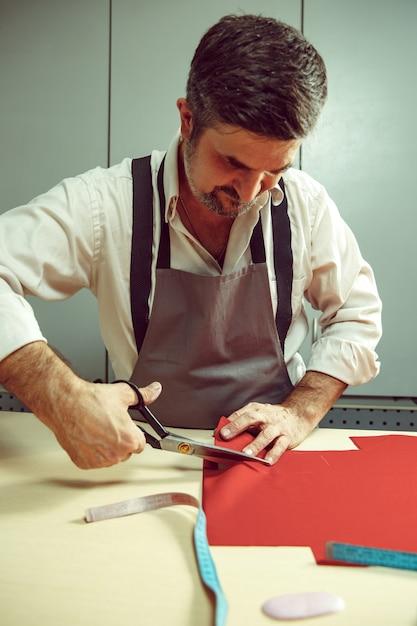 Close-up van kleermakers tafel met mannelijke handen traceren van stof maken patroon voor kleding in traditionele atelier studio. de man in vrouwelijk beroep. gendergelijkheid concept Gratis Foto