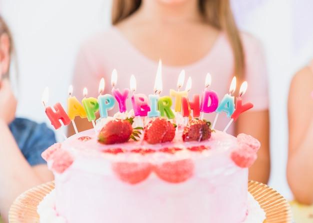 Close-up van kleurrijke gloeiende verjaardagskaarsen op de cake van het aardbeibovenste laagje Gratis Foto