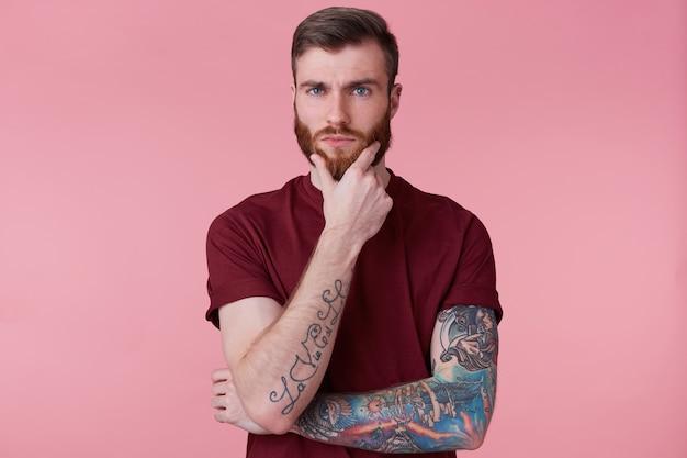 Close up van knappe doordachte bebaarde man met getatoeëerde hand, camera kijken, zijn kin vasthouden, denkt over zijn toekomst, maakt plannen, dromen, geïsoleerd op roze achtergrond. Gratis Foto