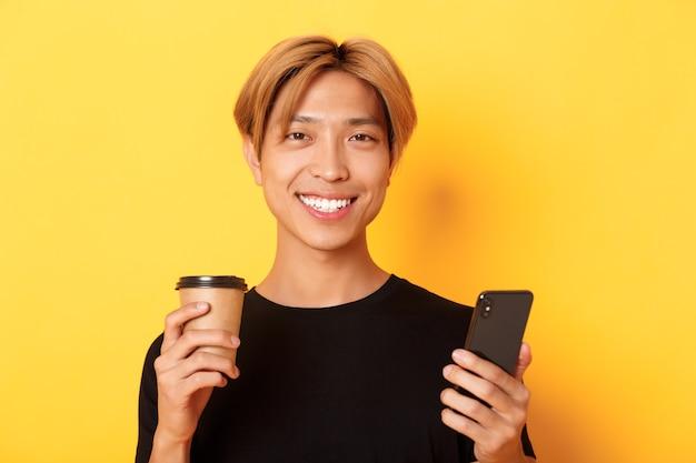 Close-up van knappe jonge aziatische kerel die gelukkig glimlacht, smartphone gebruikt en afhaalkoffie drinkt, die zich over gele muur bevindt Gratis Foto