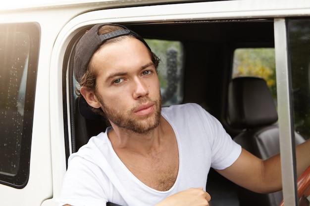 Close-up van knappe jonge man met stijlvolle baard zittend op de bestuurdersstoel in lederen cabine van zijn witte vierwielaangedreven auto en op zoek met serieuze uitdrukking tijdens road trip Gratis Foto