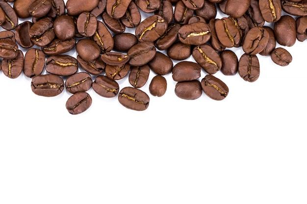 Close-up van koffiebonen op witte achtergrond. kopieer ruimte Premium Foto