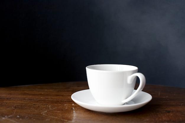 Close-up van koffiekopje op houten tafel Gratis Foto