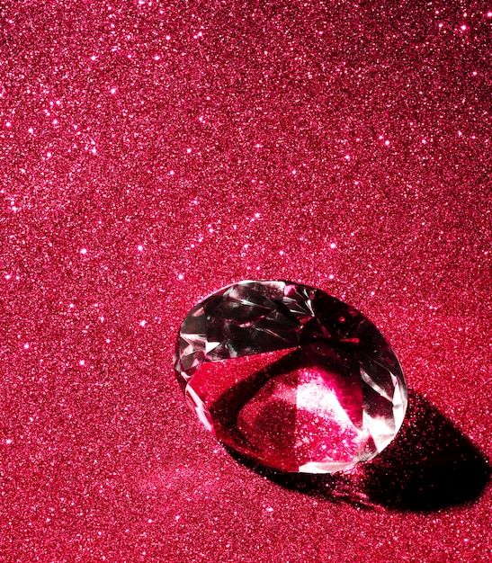 Close-up van kristal diamant op rode glanzend glitter achtergrond Gratis Foto