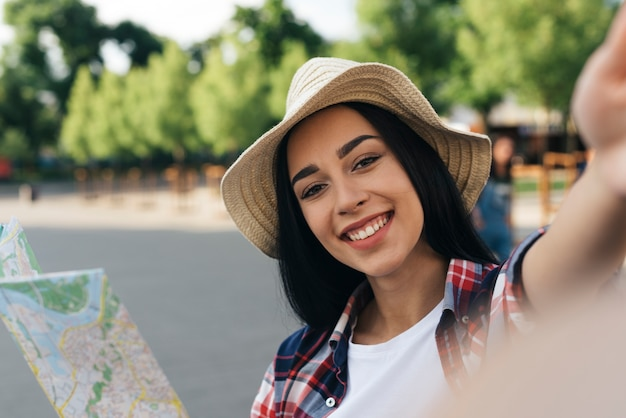 Close-up van lachende vrouw met kaart en selfie buitenshuis te nemen Gratis Foto