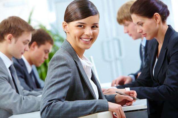 Close-up van lachende zakenvrouw met een pen Gratis Foto