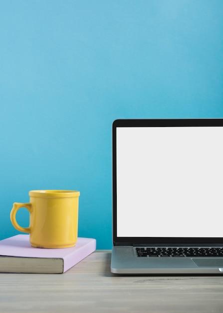 Close-up van laptop met kopje koffie en boek op houten bureau Gratis Foto