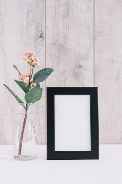 Close-up van leeg afbeeldingsframe met bloemenvaas Gratis Foto