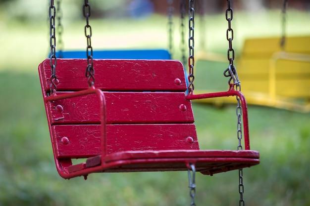 Close-up van lege houten blauwe, gele, uitstekende zetels van het multi-gekleurde carrousel hangen op kettingen. Premium Foto