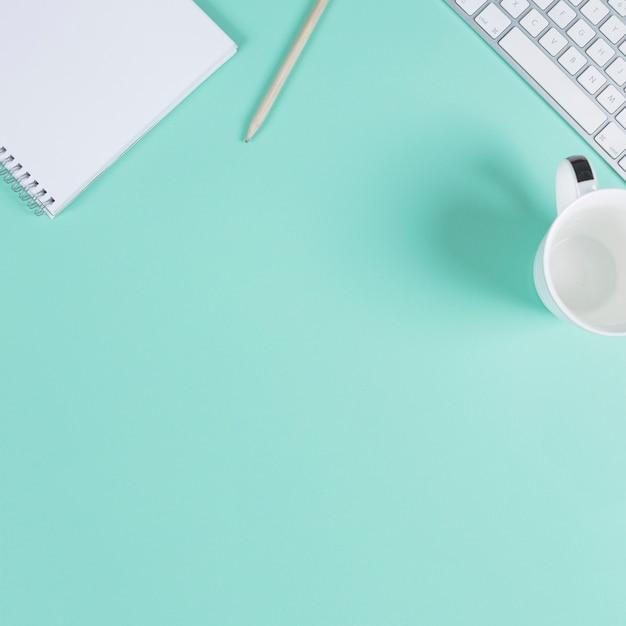Close-up van lege kladblok; potlood; beker en toetsenbord op turkooizen achtergrond met ruimte voor tekst Gratis Foto