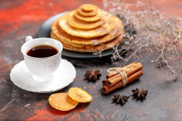 Close-up van lekker ontbijt met zachte pannenkoeken en een kopje thee naast kaneelkalk Gratis Foto