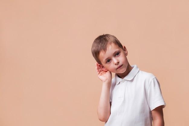 Close-up van leuke jongen die iets luistert Gratis Foto