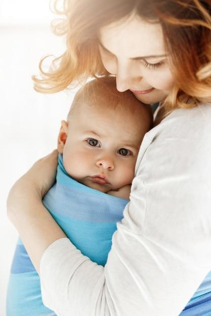 Close up van lieve kleine babyjongen met zijn grote grijze ogen. moeder knuffelt haar kind met tederheid en liefde. familie concept. Gratis Foto