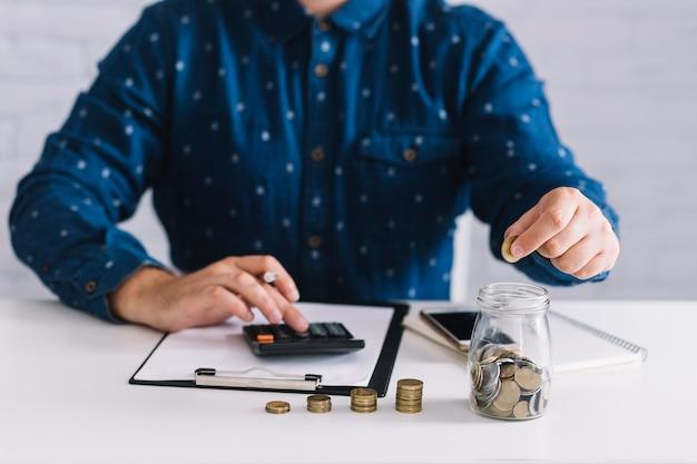 Close-up van man die winst berekenen die calculator op witte lijst gebruiken Gratis Foto
