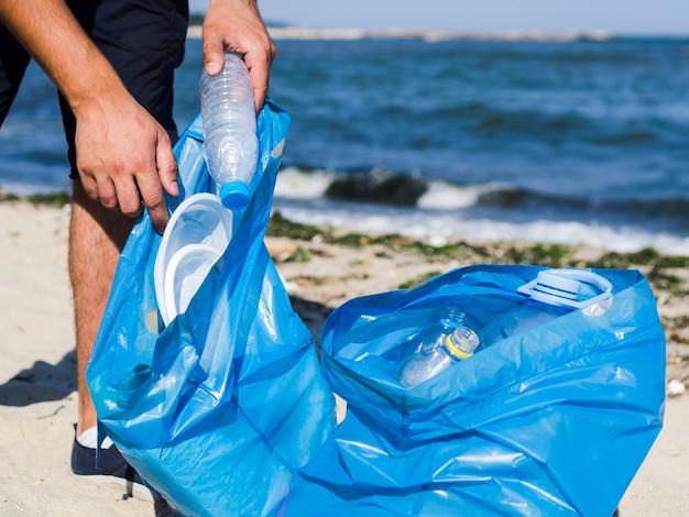 Close-up van man hand die lege plastic fles in blauwe vuilniszak op strand zet Gratis Foto