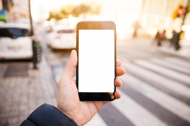 Close-up van man hand die mobiele telefoon met witte het schermvertoning op weg toont Gratis Foto