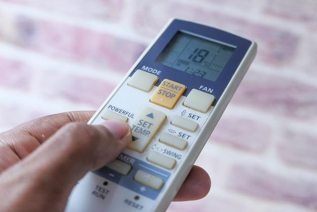 Close-up van man hand met afstandsbediening airconditioning. Premium Foto