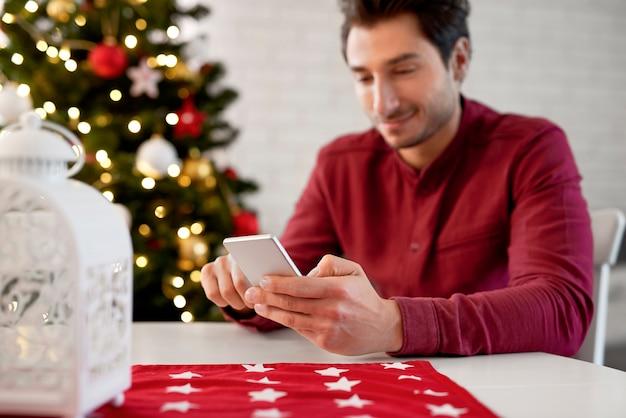 Close up van man met behulp van mobiele telefoon met kerstmis Gratis Foto