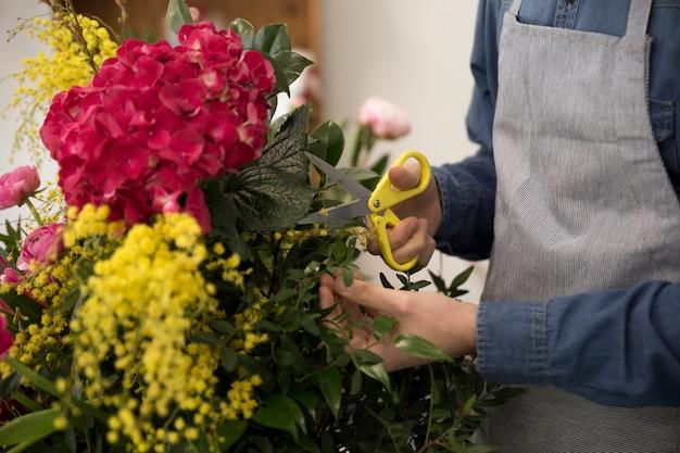 Close-up van mannelijke bloemist die de bladeren van boeket snijdt Gratis Foto