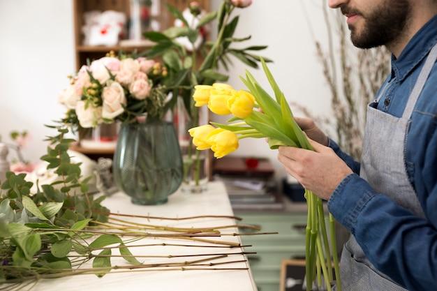 Close-up van mannelijke bloemist die de gele tulpen in de bloemwinkel schikken Gratis Foto
