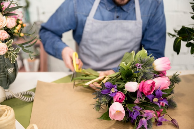 Close-up van mannelijke bloemist die het document voor het verpakken van het bloemboeket snijdt Gratis Foto