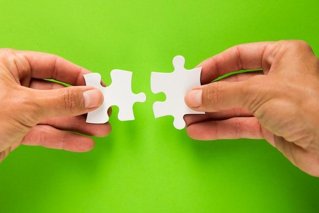 Close-up van mannelijke hand die bij wit puzzelstuk aansluit op groene achtergrond Gratis Foto