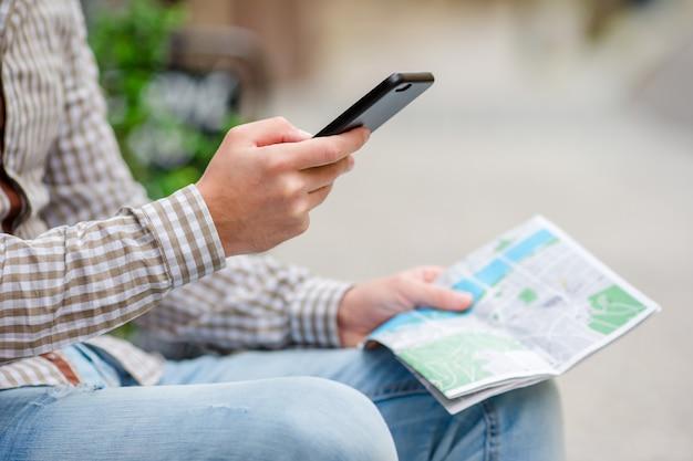 Close-up van mannelijke handen die cellphone en stadskaart in openlucht op de straat houden. man met behulp van mobiele smartphone om beroemde attractie te vinden. Premium Foto