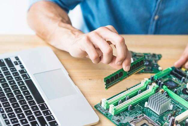 Close-up van mannelijke it-ingenieur die ram op motherboard assembleert Premium Foto