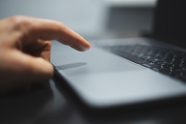 Close-up van mannenhand aanraken met vinger laptop touchpad. Premium Foto