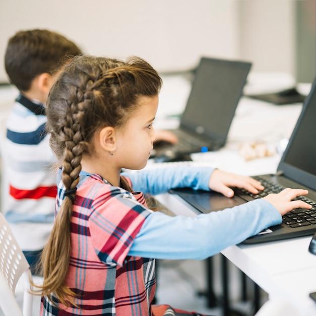 Close-up van meisje die laptop in het klaslokaal met behulp van Gratis Foto