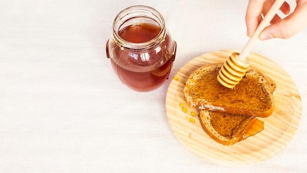 Close-up van menselijke hand het uitspreiden honing op brood die honingsdipper gebruiken Gratis Foto