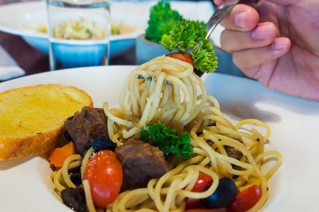 Close-up van mensen die spaghettispaghetti eten Gratis Foto