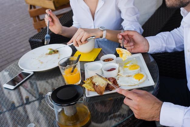 Close-up van mensen uit het bedrijfsleven handen, mannelijke en vrouwelijke ontbijten in openlucht café. maaltijden met salade, omelet, spek. Premium Foto