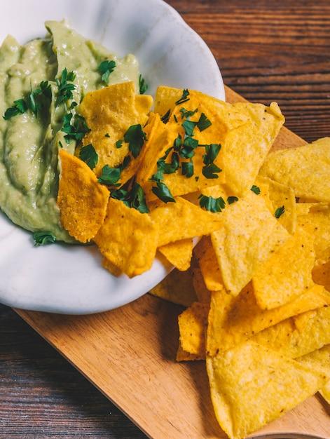 Close-up van mexicaanse nachos en guacamole in kom op houten snijplank Gratis Foto