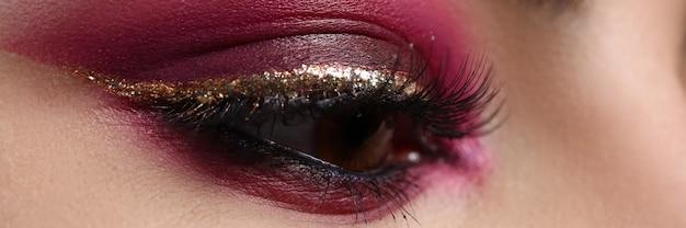 Close-up van mooi vrouwelijk oog met sexy gouden voering. make-up en cosmetica concept. macro-opname van glanzende oogschaduw op mooie dame. schoonheid perfect gezicht en foundation Premium Foto
