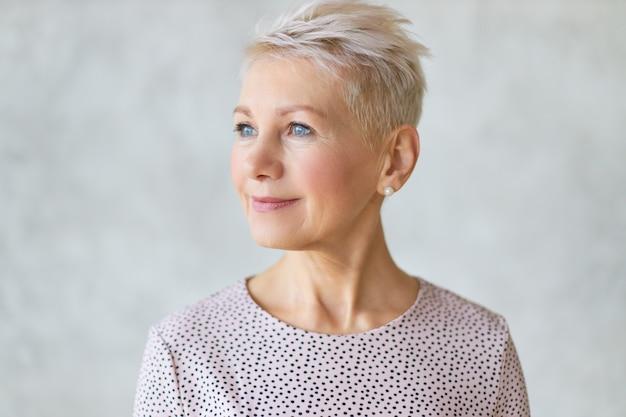 Close-up van mooie aantrekkelijke europese dame van middelbare leeftijd met stijlvol kapsel en nette make-up wegkijken met zelfverzekerde glimlach poseren geïsoleerd tegen een marmeren muur Gratis Foto