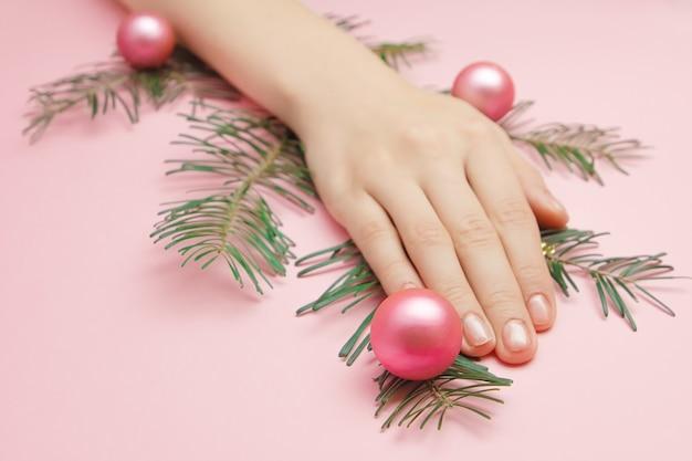 Close-up van mooie dames handen met een kerstboomtak met roze ballen Premium Foto