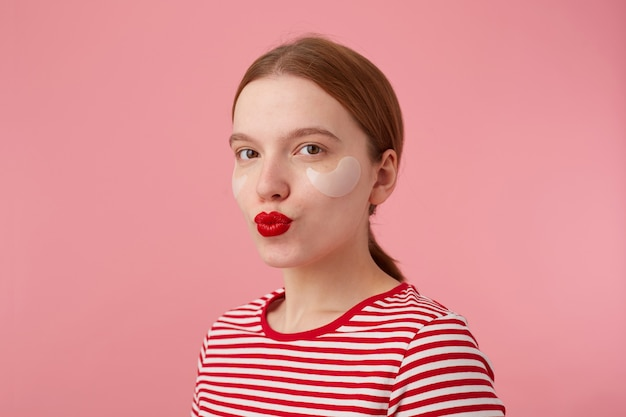 Close-up van mooie jonge lachende roodharige dame met rode lippen en met vlekken onder de ogen, draagt in een rood gestreept t-shirt, kijkt en stuurt kus, staat. Gratis Foto